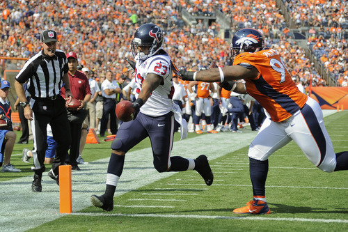 Houston Texans running back Arian Foster (23) scores a touchdown against Denver Broncos defensive tackle Kevin Vickerson (99) in the first quarter of an NFL football game Sunday, Sept. 23, 2012, in Denver. (AP Photo/Jack Dempsey)