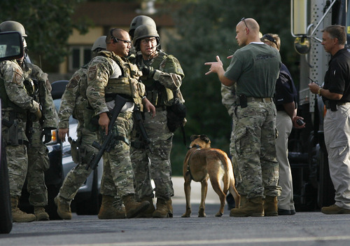 Scott Sommerdorf  |  The Salt Lake Tribune              Unified Police SWAT officers discuss possible approaches as they respond to a report of a man barricaded in his home with possible explosives at 3128 Del Mar in Millcreek, Sunday, September 23, 2012.