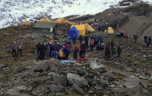 In this photo provided by Nepalese airline Simrik Air, rescuers attend to injured victims, unseen, after an avalanche at the base camp of Mount Manaslu in northern Nepal, Sunday, Sept. 23, 2012. The avalanche swept away climbers on a Himalayan peak in Nepal on Sunday, leaving at least nine dead and six others missing, officials said. (AP Photo/Simrik Air)