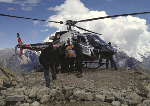 In this photo provided by Nepalese airline Simrik Air, an injured victim of an avalanche is carried to a helicopter after being rescued at the base camp of Mount Manaslu in northern Nepal, Sunday, Sept. 23, 2012. The avalanche swept away climbers on a Himalayan peak in Nepal on Sunday, leaving at least nine dead and six others missing, officials said. (AP Photo/Simrik Air)