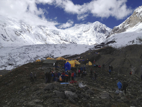 In this photo provided by Nepalese airline Simrik Air, rescuer attend to injured victims, unseen, in an avalanche at the base camp of Mount Manaslu in northern Nepal, Sunday, Sept. 23, 2012. The avalanche swept away climbers on a Himalayan peak in Nepal on Sunday, leaving at least nine dead and six others missing, officials said. (AP Photo/Simrik Air)