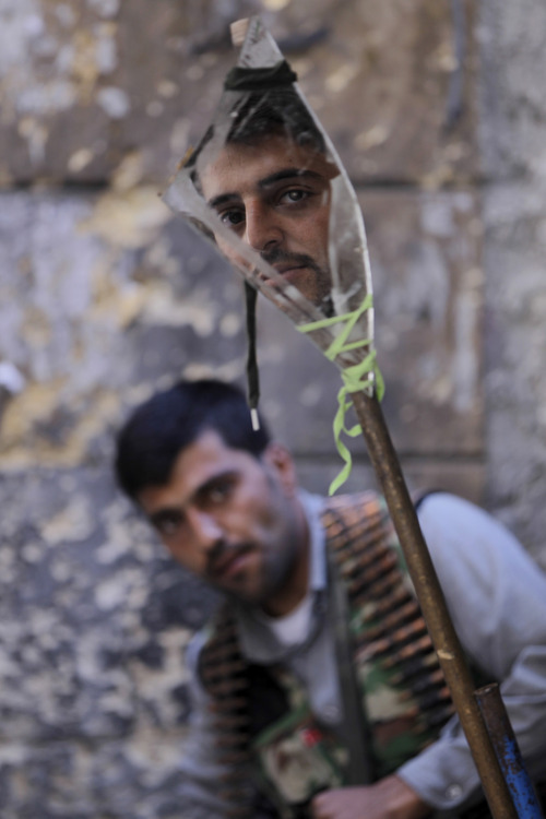 A Free Syrian Army soldier, foreground, looks at a mirror which helps him see Syrian troops on the other side, as he takes his position with his comrade during their fighting against the Syrian troops, at the old city of Aleppo city, Syria, Monday Sept. 24, 2012. Syrian warplanes bombed two buildings on Monday in the northern city of Aleppo, killing at least five people including three children from the same family, activists said. (AP Photo/Hussein Malla)