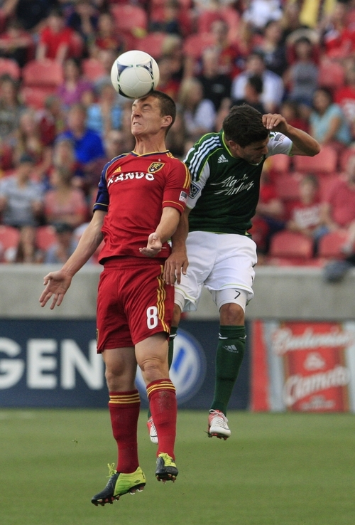 Real Salt Lake midfielder Will Johnson (8) heads the ball as Portland Timbers midfielder Sal Zizzo defends in the first half of an MLS soccer game Saturday, Sept. 22, 2012, in Sandy, Utah.  (AP Photo/Rick Bowmer)