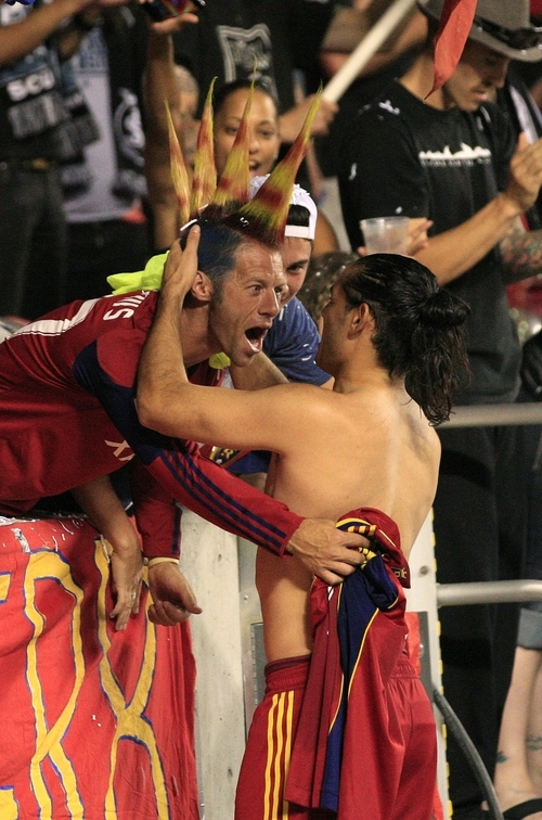 Real Salt Lake forward Fabian Espindola receives a hug from Randolf Scott, a fan, at the end of their MLS soccer game with the Portland Timbers Saturday, Sept. 22, 2012, in Sandy. Real Salt Lake defeated the Portland Timbers 2-1. (AP Photo/Rick Bowmer)