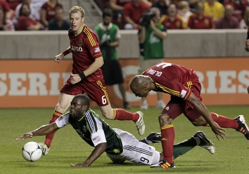 Portland Timbers forward Bright Dike (19) falls as Real Salt Lake defender Jamison Olave (4) defends as teammate Nat Borchers (6) looks on in the second half of an MLS soccer game Saturday, Sept. 22, 2012, in Sandy, Utah. Real Salt Lake defeated Portland Timbers 2-1.   (AP Photo/Rick Bowmer)