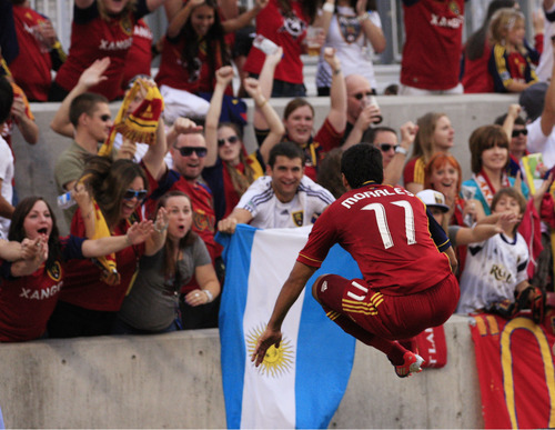 Real Salt Lake midfielder Javier Morales (11) leaps in the air as he hurdles a barricade to celebrate with fans after scoring against the Portland Timbers in the first half of an MLS soccer game, Saturday, Sept. 22, 2012, in Sandy.  (AP Photo/Rick Bowmer)