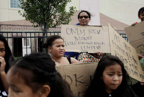 Ashley Detrick     The Salt Lake Tribune Eva Kamitoni protests with her children and several others from the Tongan United Methodist Church on Sunday September 23, 2012.  Members of the West Valley City church protested the temporary removal of their pastor, Rev. Havili Mone. The members are upset that they were not given an explanation for the move and that the replacement pastor locked members out of the church last week.