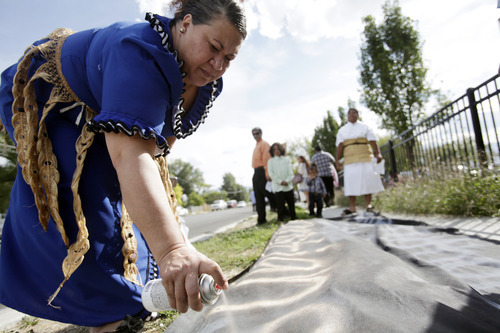 Ashley Detrick     The Salt Lake Tribune Saane Lotaki spray paints a sign that says