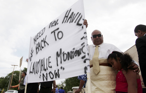 Ashley Detrick     The Salt Lake Tribune Lyndon Lauhingoa stands with his daughter and dozens of others during a protest outside the Tongan United Methodist Church on Sunday September 23, 2012.  Members of the West Valley City church protested the temporary removal of their pastor, Rev. Havili Mone. The members are upset that they were not given an explanation for the move and that the replacement pastor locked members out of the church last week.