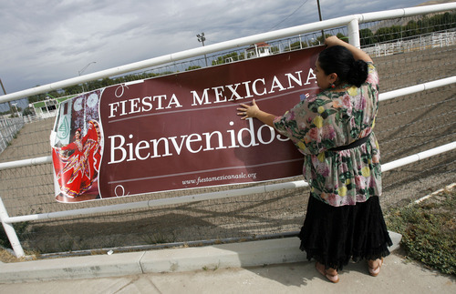 Francisco Kjolseth  |  The Salt Lake Tribune Anita Watson, event coordinator for Fiesta Mexicana at the state fair, puts up a banner to draw attention to the event.