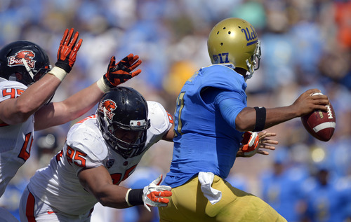 UCLA quarterback Brett Hundley, right, tries to pass under pressure from Oregon State defensive end Dylan Wynn, left, and defensive end Scott Crichton during the first half of their NCAA college football game, Saturday, Sept. 22, 2012, in Pasadena, Calif. (AP Photo/Mark J. Terrill)