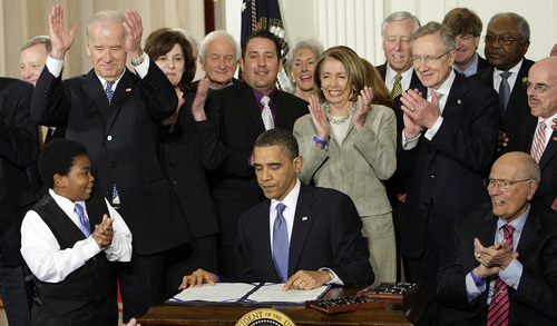 FILE - In this March 23, 2010, file photo, participants applaud in the East Room of the White House in Washington, Tuesday, March 23, 2010, as President Barack Obama, flanked by Macelas Owens of Seattle, left, and Rep. John Dingell, D-Mich., right, signs the health care bill. Americans may not be all that crazy about President Barack Obama's health care law, but a new poll shows they don't see it going away. The Associated Press-GfK poll finds that about 7 in 10 Americans think the overhaul law will go into effect fully, with some changes, ranging from minor to major alterations. Behind the president, from left are, Senate Majority Whip Richard Durbin of Ill., Vice President Joe Biden, Vicki Kennedy, widow of Sen. Ted Kennedy, Rep. Sander Levin, D-Mich., Ryan Smith of Turlock, Calif., Health and Human Services Kathleen Sebelius, House Speaker Nancy Pelosi of Calif., House Majority Leader Steny Hoyer of Md., Senate Majority Leader Harry Reid of Nev., Rep. Patrick Kennedy, D-R.I., House Majority Whip James Clyburn of S.C., and Rep. Henry Waxman, D-Calif.  (AP Photo/J. Scott Applewhite, File)
