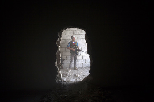 Free Syrian Army fighter takes cover in a building during clashes against the Syrian Army in Aleppo, Syria, Tuesday, Sept. 25, 2012. Over the past few months, rebels have increasingly targeted security sites and symbols of regime power in a bid to turn the tide in Syria's 18-month conflict, which activists say has left some 30,000 people dead. (AP Photo/Manu Brabo)