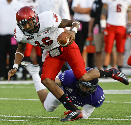 Weber State's Willie Harris (29) trips up Eastern Washington's Vernon Adams (16) during an NCAA college football game in Ogden, Utah, on Saturday, Sept. 22, 2012. (P Photo/Standard-Examiner, Nicholas Draney) TV OUT  LOCAL TV  OUT  MANDATORY CREDIT