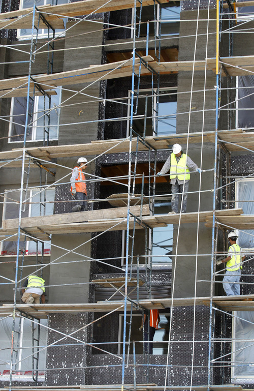 Al Hartmann  |  The Salt Lake Tribune Construction workers work on scaffolding on the new urban community called Birkhill on Main. The $45 million multi-phase mixed-use development consists of high-density apartments and retail and office space. These amenities are positioned near Murray's light rail station, and the upcoming commuter-rail line to Provo that starts operating this December. Phase 1 of Birkhill on Main, a $17 million project at 4255 S. Main rises five stories and when finished will feature 137 one- to three-bedroom apartments ranging in size from 664 to 1119 square feet.