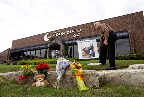 Lynn Meredith, who works at the Moon River Theater, places a photo of Andy Williams in front of Andy Williams Moon River Grill on Wednesday, Sept. 26, 2012, in Branson, Mo. Williams, who became a major star in 1956, died Tuesday night at his Branson area home, according to his publicist Paul Shefrin. Williams announced last year that he had bladder cancer. (AP Photo/David Welker)