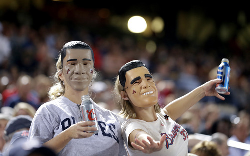 Fans wearing masks of President Barack Obama, left, and Republican presidential candidate, former Massachusetts Gov. Mitt Romney, right, watch a baseball game between the Atlanta Braves and the Miami Marlins Tuesday, Sept. 25, 2012, in Atlanta. (AP Photo/David Goldman)
