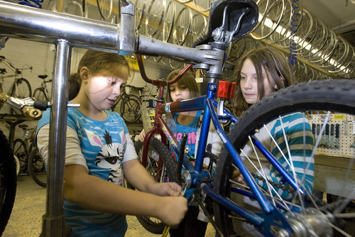 Paul Fraughton | Salt Lake Tribune Cianne Paul,age10, Angel Martinez,10, and Katie Johnson team up to work on a bike at the Bicycle Collective.   Thursday, September 27, 2012