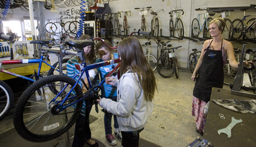 Paul Fraughton | Salt Lake Tribune Hailey Broussard who works at the Bicycle Collective's Build a Bike program watches as  youngsters  from Youth City Central City work on a bicycle.   Thursday, September 27, 2012