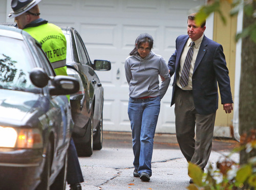 Annie Dookhan, center, is escorted to a cruiser outside her home in Franklin, Mass., Friday, Sept. 28, 2012. Dookhan is accused of faking drug results, forging signatures and mixing samples a state police lab. State police say Dookhan tested more than 60,000 drug samples involving 34,000 defendants during her nine years at the lab. Defense lawyers and prosecutors are scrambling to figure out how to deal with the fallout.  (AP Photo/Bizuayehu Tesfaye)