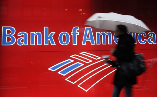 FILE - In this Dec. 7, 2011 file photo, a woman passes a Bank of America office branch, in New York. Bank of America said Friday, Sept. 28, 2012 that it has agreed to pay $2.43 billion to settle a class-action lawsuit related to its acquisition of Merrill Lynch at the height of the financial crisis. (AP Photo/Mark Lennihan, File)