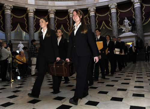 FILE - In this Jan. 8, 2009 file photo, Capitol Hill Pages carry a box of the Electoral College votes to the House Chamber to be certified, on Capitol Hill in Washington. When it comes to voting for president, not all votes are created equal. Chances are yours will count less than a select few. Each state's Electoral College votes are based on the size of its congressional delegation, not its population. Because of that, a presidential vote in Wyoming mathematically counts more than three times as much as a vote in Ohio, at least in terms of choosing electors.  (AP Photo/Susan Walsh, File)