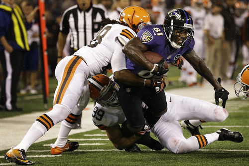 Cleveland Browns free safety Usama Young, left, and outside linebacker Scott Fujita (99) stop Baltimore Ravens wide receiver Anquan Boldin (81) during the second half of an NFL football game in Baltimore, Thursday, Sept. 27, 2012. (AP Photo/Patrick Semansky)