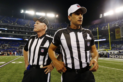 Referee Gene Steratore, right, and back judge Bob Waggoner, left, look around the field before an NFL football game between the Baltimore Ravens and Cleveland Browns in Baltimore, Thursday, Sept. 27, 2012. (AP Photo/Patrick Semansky)