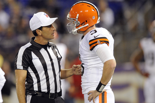 Referee Gene Steratore talks with Cleveland Browns quarterback Brandon Weeden before an NFL football game against the Baltimore Ravens in Baltimore, Thursday, Sept. 27, 2012. (AP Photo/Nick Wass)
