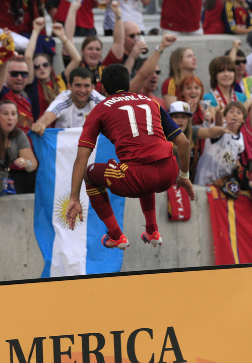 Real Salt Lake's Javier Morales (11) leaps in the air as he huddles a barricade to celebrate with fans after scoring against the Portland Timbers in the first half of an MLS soccer game Saturday, Sept. 22, 2012, in Sandy, Utah. (AP Photo/Rick Bowmer)