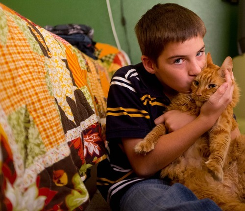 Trent Nelson  |  The Salt Lake Tribune Michael Chambers kisses his foster mom's cat in his bedroom at the foster home where he lives in Eagle Mountain, Utah. Due to the lack of services for children with autism, a small number of families are turning their children, like Chambers, over to the child welfare system each year desperate for the services they can get in state custody.