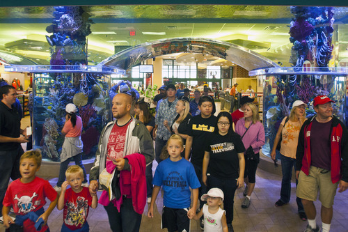 Chris Detrick  |  The Salt Lake Tribune Customers enter Scheels as it opens for the first time Saturday September 29, 2012. Scheels opened its 220,000-square-foot mega-sporting goods store in Sandy. Featuring a 16-car Ferris wheel rising toward a skylight, a 16,000-gallon double-arched salt water aquarium, a boating department, game centers and a focus on fashionable apparel, the store is meant to be a fun destination, said Dan Hermanson, an assistant store leader.