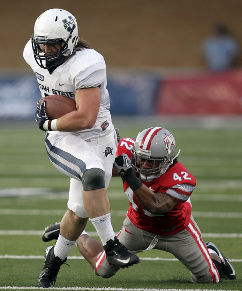 Utah State tight end Kellen Bartlett (81) breaks the tackle of UNLV defensive back Peni Vea (42) in the first quarter of an NCAA college football game Saturday, Sept. 29, 2012, in Logan, Utah.  (AP Photo/Rick Bowmer)