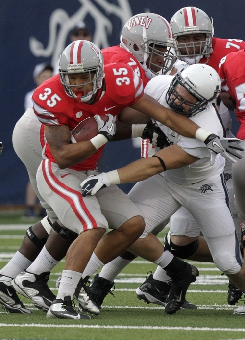 UNLV running back Tim Cornett (35) is tackled by Utah State defensive lineman B.J. Larsen (99) in the first quarter of an NCAA college football game Saturday, Sept. 29, 2012, in Logan, Utah.  (AP Photo/Rick Bowmer)