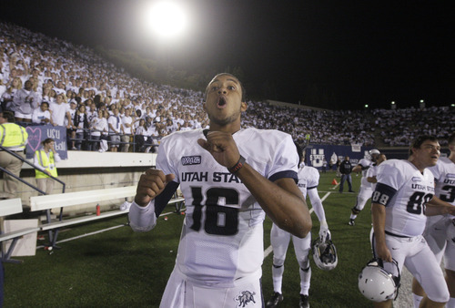 Utah State quarterback Chuckie Keeton (16) celebrates on the sidelines during the fourth quarter of an NCAA college football game against UNLV on Saturday, Sept. 29, 2012, in Logan, Utah. (AP Photo/Rick Bowmer)