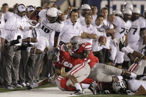 Utah State wide receiver Chuck Jacobs (10) knocked out of bounds by UNLV's Anthony Williams (6) and David Greene (22) in the fourth quarter of an NCAA college football game Saturday, Sept. 29, 2012, in Logan, Utah. Utah State defeated UNLV 35-13.  (AP Photo/Rick Bowmer)