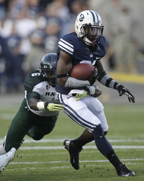 Brigham Young running back Jamaal Williams (21) carries the ball as Hawaii linebacker Darryl McBride Jr. (6) closes in for a tackle during the first quarter of an NCAA college football game Friday, Sept. 28, 2012, in Provo, Utah. (AP Photo/Rick Bowmer)