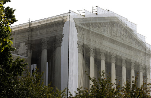 Workers cover the U.S. Supreme Court building in Washington Thursday, Sept. 27, 2012, with a protective scrim, as work continues on the facade. The Supreme Court is embarking on a new term beginning Monday that could be as consequential as the last one with the prospect for major rulings about affirmative action, gay marriage and voting rights. (AP Photo/Alex Brandon)