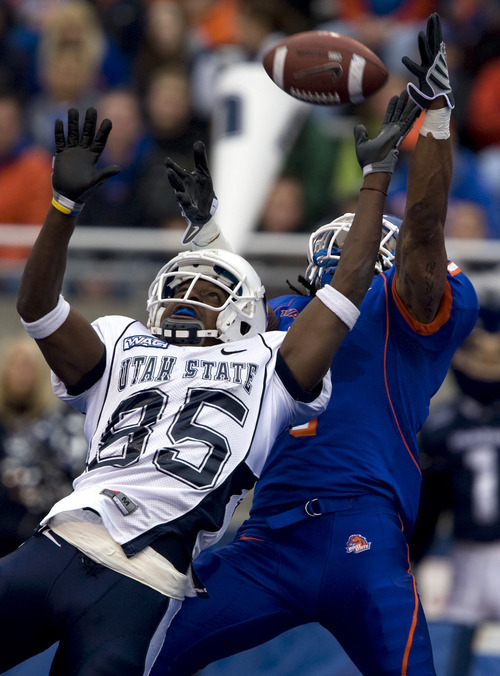 Boise State's Kyle Wilson, right, knocks the ball away from Utah State's Omar Sawyer (85) during the second half of an NCAA college football game on Saturday, Nov. 8, 2008 in Boise, Idaho.  (AP Photo/Matt Cilley)
