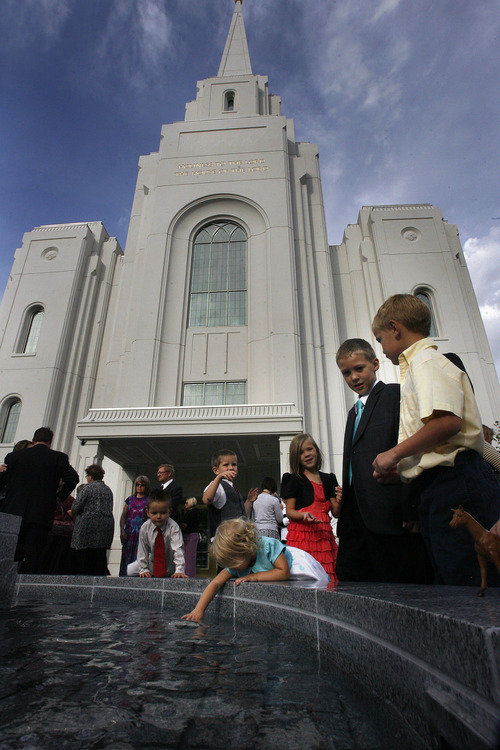 Scott Sommerdorf  |  The Salt Lake Tribune              Melia Christensen, 2, plays in the fountain utside the newly-dedicated Brigham City temple, along with other Christensen brothers and cousins, September 23, 2012.