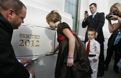 Scott Sommerdorf  |  The Salt Lake Tribune              Seven year old Aliya Purcell helps apply some mortar to the cornerstone as her brother Jabob, 3, and the rest of her family watches. The new temple in Brigham City was dedicated, at 250 South Main Street, Sunday, September 23, 2012.