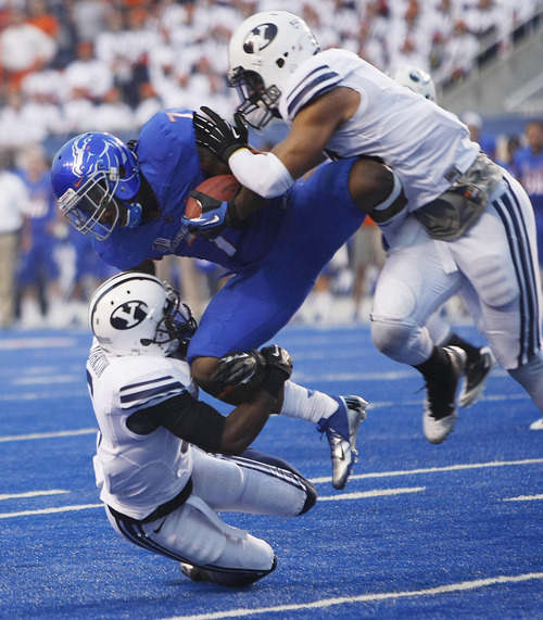 Boise State running back D.J. Harper is brought down by Brigham Young defenders Jordan Johnson, left, and Kyle Van Noy during an NCAA college football game Thursday, Sept. 20, 2012, in Boise, Idaho. (AP Photo/The Idaho Statesman, Darin Oswald)