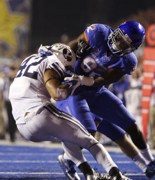 Samuel Ukwuachu #82 of the Boise State Broncos brings down Michael Alisa #42 of the BYU Cougars at Bronco Stadium on Thursday September 20, 2012.