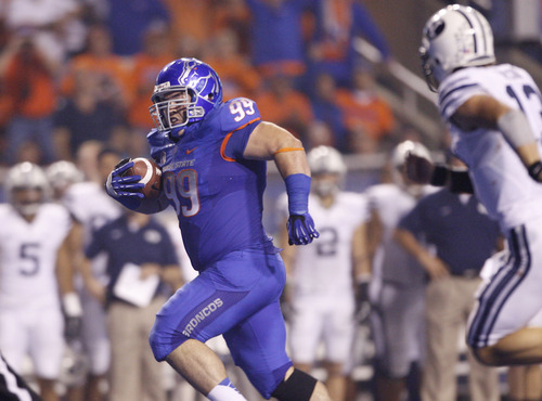 Boise State's Michael Atkinson returns an interception for a touchdown, outrunning quarterback Brigham Young quarterback Riley Nelson during an NCAA college football game Thursday, Sept. 20, 2012, in Boise, Idaho. (AP Photo/The Idaho Statesman, Joe Jaszewski)