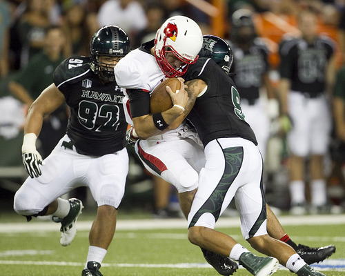 Lamar quarterback Ryan Mossakowski, center, gets sacked by Hawaii defensive back Bubba Poueu-Luna, right,  and defensive lineman Beau Yap, left, during the second quarter of the NCAA game between the Lamar and Hawaii, Sept. 15, 2012 in Honolulu.  (AP Photo/Marco Garcia)