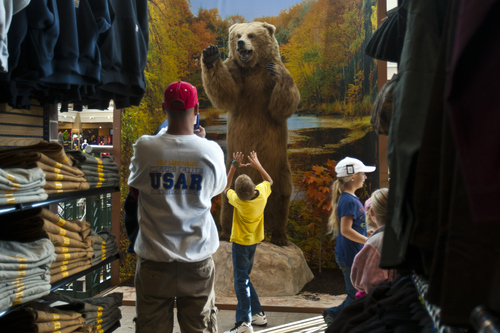 Chris Detrick  |  The Salt Lake Tribune Customers pose for pictures with a bear on display at Scheels on  Sept. 29, 2012. Scheels opened its 220,000-square-foot mega-sporting goods store in Sandy. Featuring a 16-car Ferris wheel rising toward a skylight, a 16,000-gallon double-arched salt water aquarium, a boating department, game centers and a focus on fashionable apparel, the store is meant to be a fun destination, said Dan Hermanson, an assistant store leader.