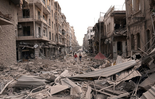 In this photo released by the Syrian official news agency SANA, Syrian men walk at a street between destroyed buildings where triple bombs rocked at the Saadallah al-Jabri square, in Aleppo city, Syria, Wednesday Oct. 3, 2012. Three powerful explosions rocked the main square in a government-controlled central district of Aleppo on Wednesday, the Syrian state-run TV said. Activists reported multiple casualties and heavy material damage. (AP Photo/SANA)