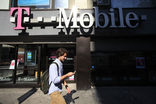 FILE-In this Wednesday, Sept. 12, 2012, file photo  man using a cellphone passes a T-Mobile store, Wednesday, Sept. 12, 2012 in New York. Struggling cellphone companies T-Mobile USA and MetroPCS Communications are set to merge, in a deal that will create an operator with more than 40 million subscribers. In a joint statement, the two companies said Wednesday, Oct. 3, 2012, that Deutsche Telekom AG, the owner of T-Mobile USA, will hold 74 percent of the new business, while MetroPCS's shareholders will hold the remainder, as well as receiving a payment of about $1.5 billion. (AP Photo/Mark Lennihan, File)