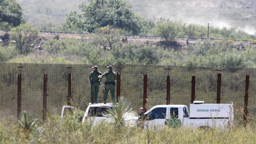 U.S. Border Patrol agents stand on top of their vehicles and look into Mexico west of Douglas, Ariz., after a Border Patrol agent was shot and killed on Tuesday Oct. 2, 2012. One agent was killed and another wounded in the incident.    (AP Photo/Arizona Daily Star, Benjie Sanders)