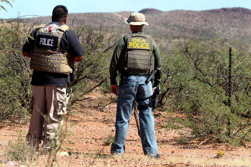 Det. Bill Silva, left, with the Bisbee Police Department, and an unnamed agent with the Drug Enforcement Administration patrol a fence line east of Naco, Ariz., after a Border Patrol agent was killed early Tuesday, Oct. 2, 2012. The shooting occurred after an alarm was triggered on one of the thousands of sensors placed by the U.S. government along the border, and the agents went to investigate, said Cochise County Sheriff's spokeswoman Carol Capas. (AP Photo/Arizona Daily Star, Mike Christy)